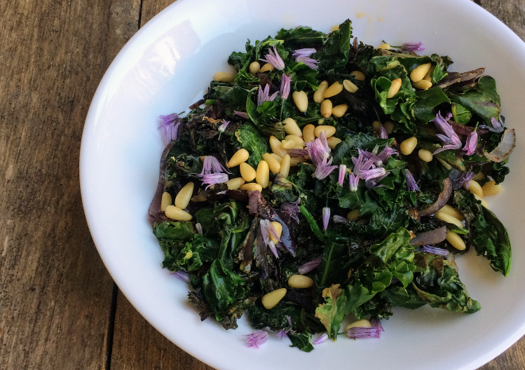 Sauteed kale and red onions garnished with pine nuts and edible chive blossoms