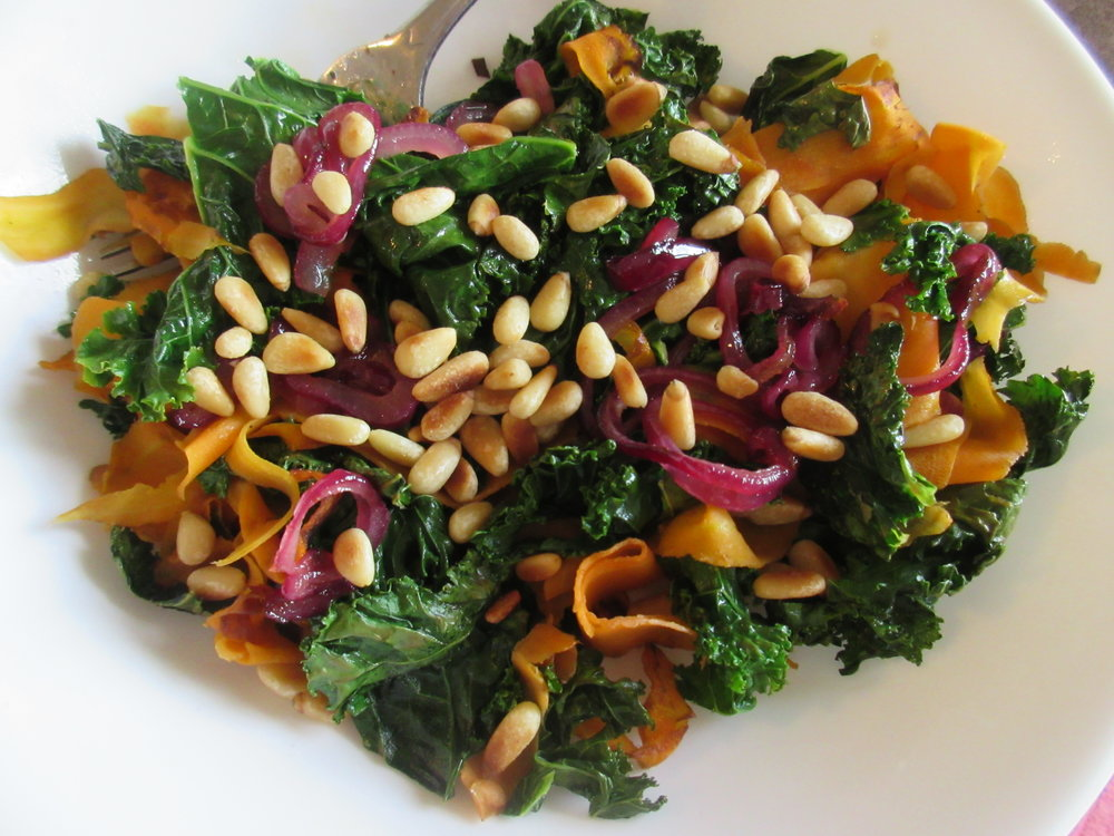 Sauteed kale with purple onions and carrot ribbons (made using a vegetable peeler) and garnished with pine nuts.