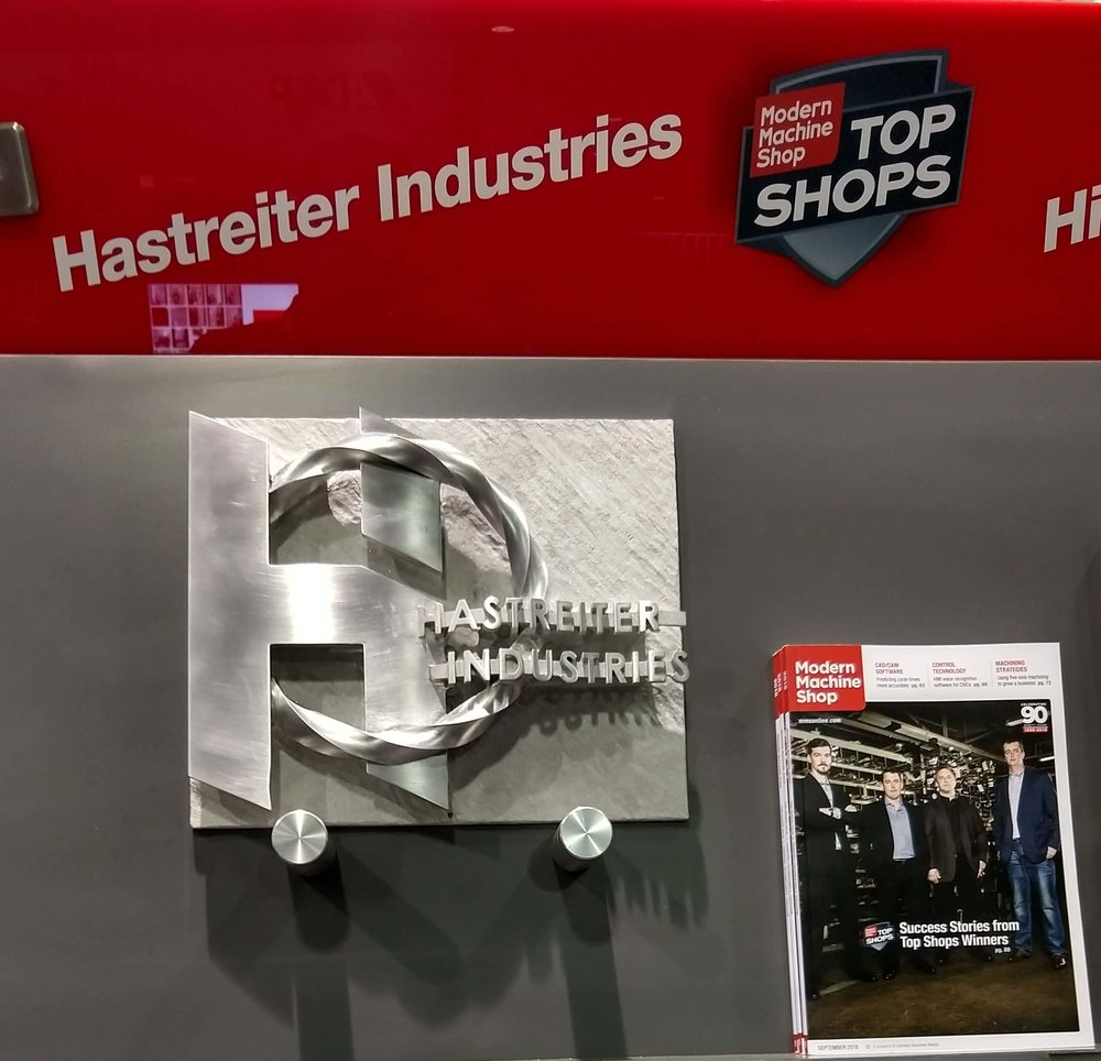 Hastreiter Industries joined the  Top Shop Hall of Fame , as one one of Modern Machine Shop's 2018 Top Shop for all of the United States. The logo pictured was machined in  a single operation  from solid aluminum on one of our 5 axis CNC mills. The upper right corner of the braid is 100% complete on its backside and not attached to the back plate.