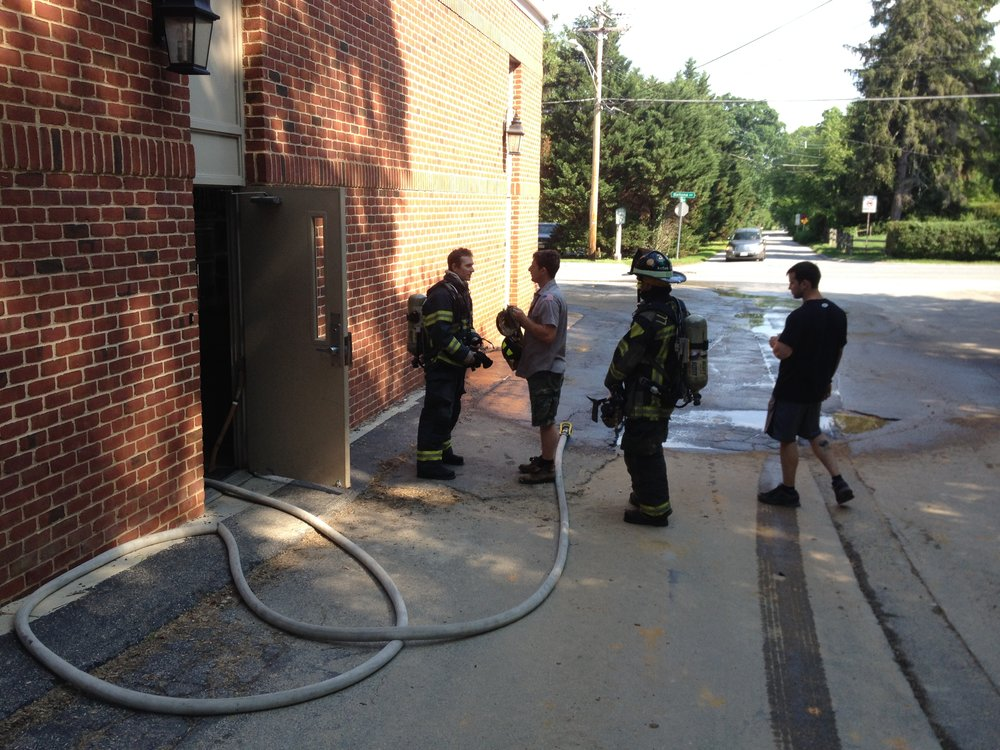 "Members conduct simple hose deployment but are wearing full PPE and SCBA to add realism. The evolution used this entrance door in reverse to add obstacles to deploy around. The ""inside"" of the structure was the actual outside."