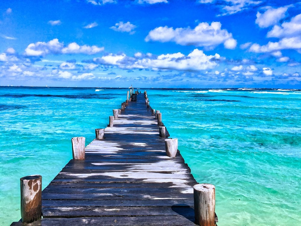 A narrow wooden pier jutting out into a turquoise ocean. Blue sky filled with puffy clouds is overhead.