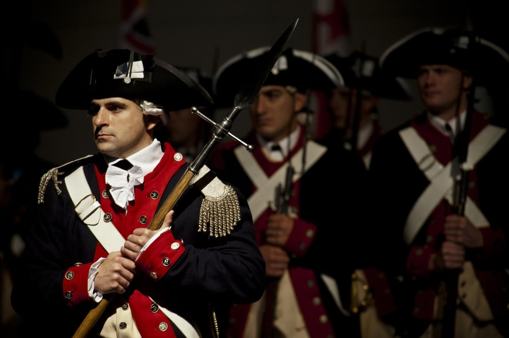 Revolutionary War soldiers standing while clutching muskets.