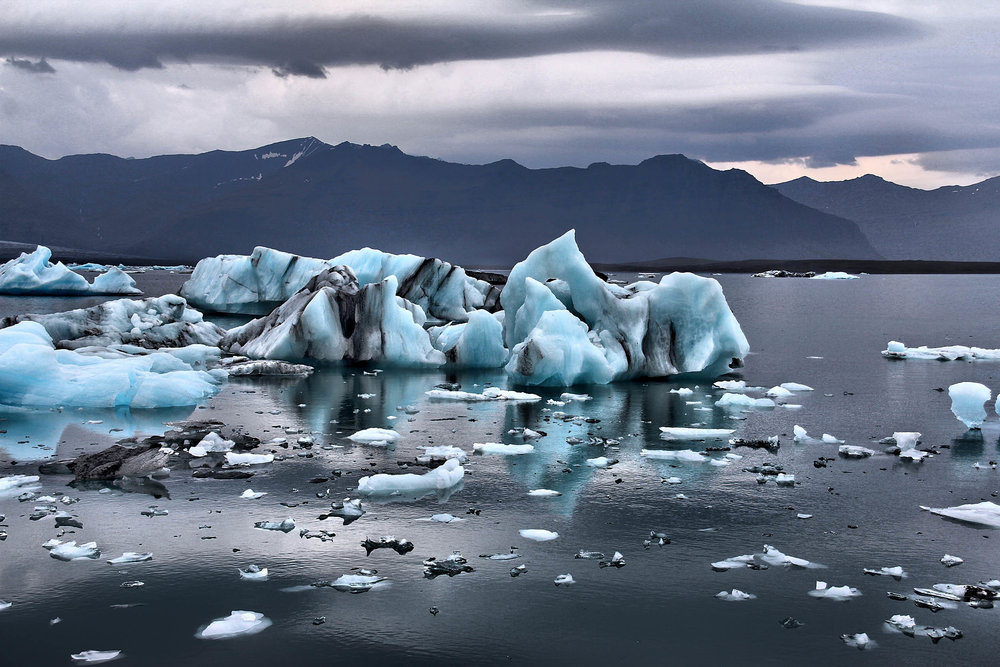 Small white, blue & black icebergs in an icy lake