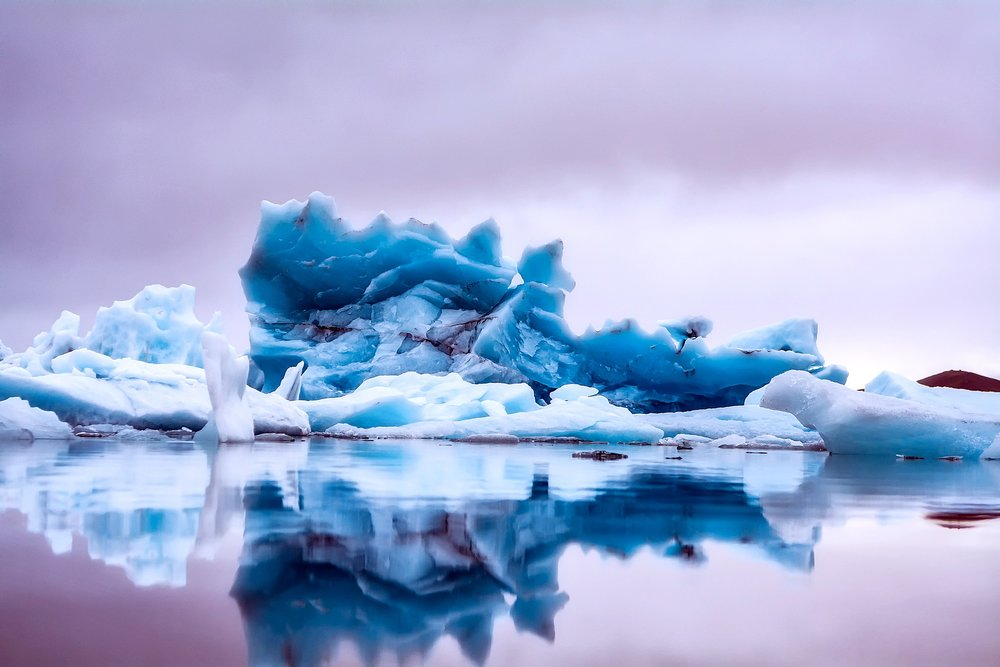 An Icelandic glacier reflected on still water in striking colors.