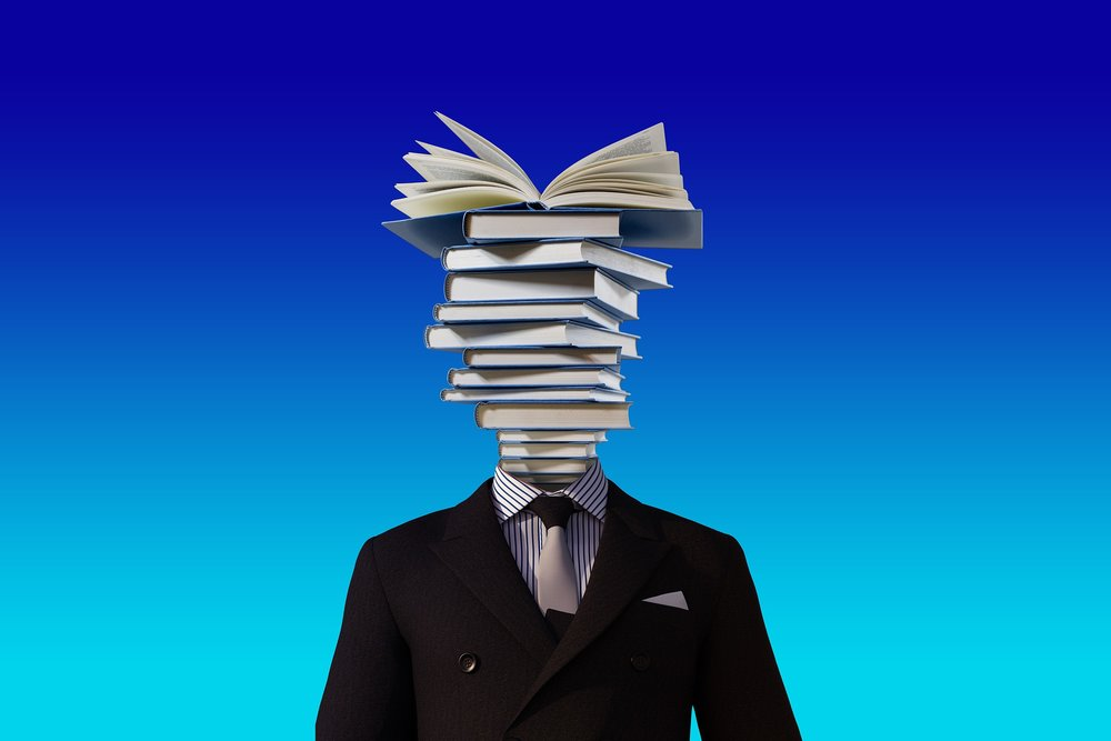 A man's body with a stack of books in lieu of a head.