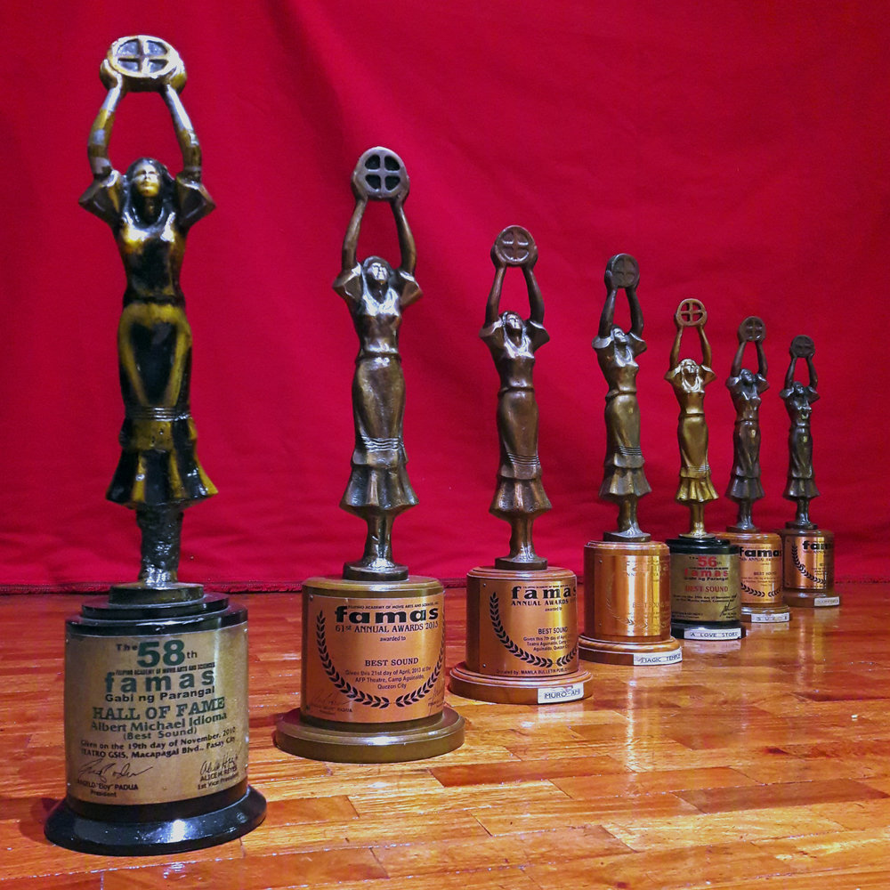 The award statuette - modeled after the actress Rosa Rosal, features a woman with her raised hands holding a film reel standing over a cylindrical pedestal with the award name written in bold black letters. -