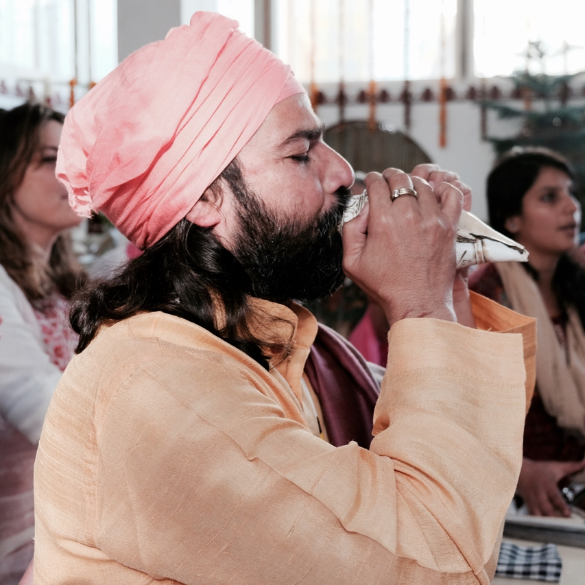 Yogrishi Vishvketu plays his conch at Akhanda Yoga Ashram