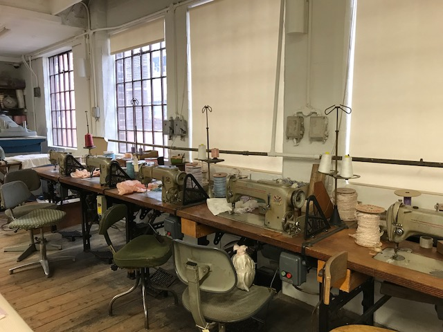 A row of sewing machines where seamstresses sat for 12 hours a day making coffin shrouds.