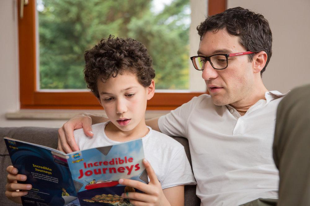 sandra ruth stuttgart family photographer Boy Reading Book To Dad.jpg