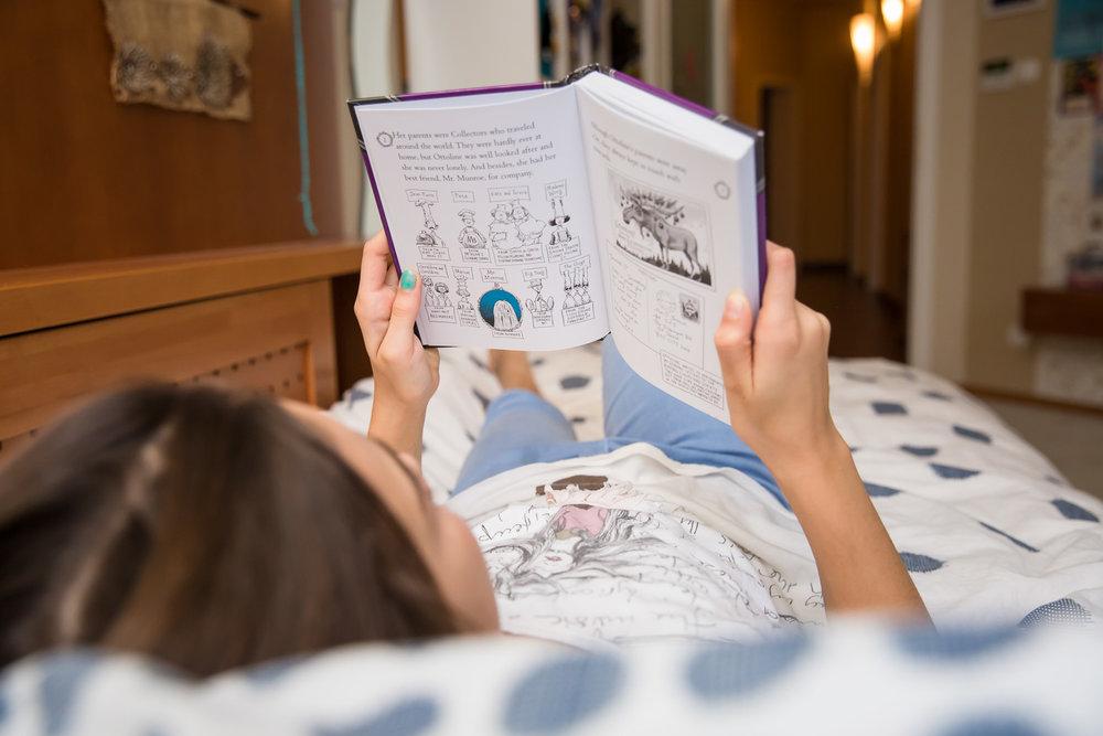 sandra ruth stuttgart family photographer Girl Reading Book In Bed.jpg