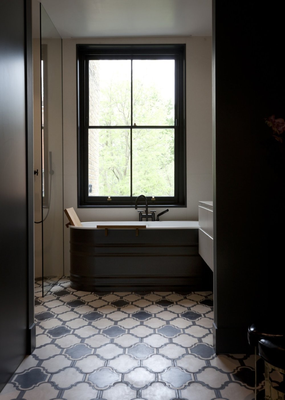 On the floor of the main bathroom, the  Lantern  model from Popham Design echoes the large black window frame and the black fittings.