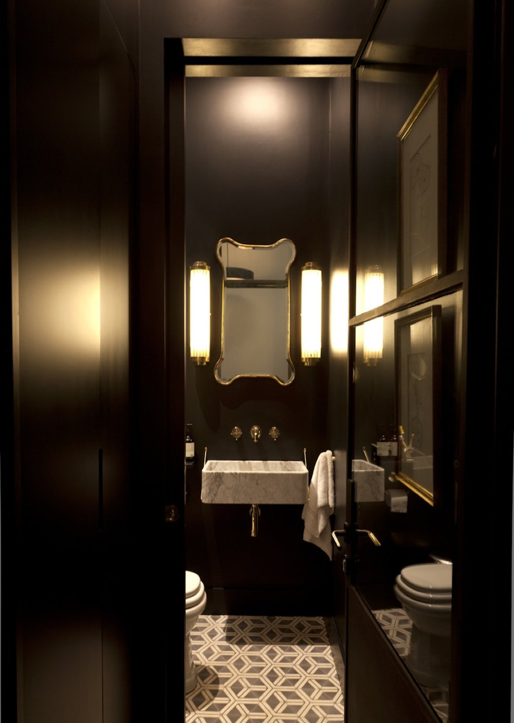 The powder room becomes glamorous in black and golden touches. Linking the hallway and the study, the Hex Arrow brings the final touch to the space.