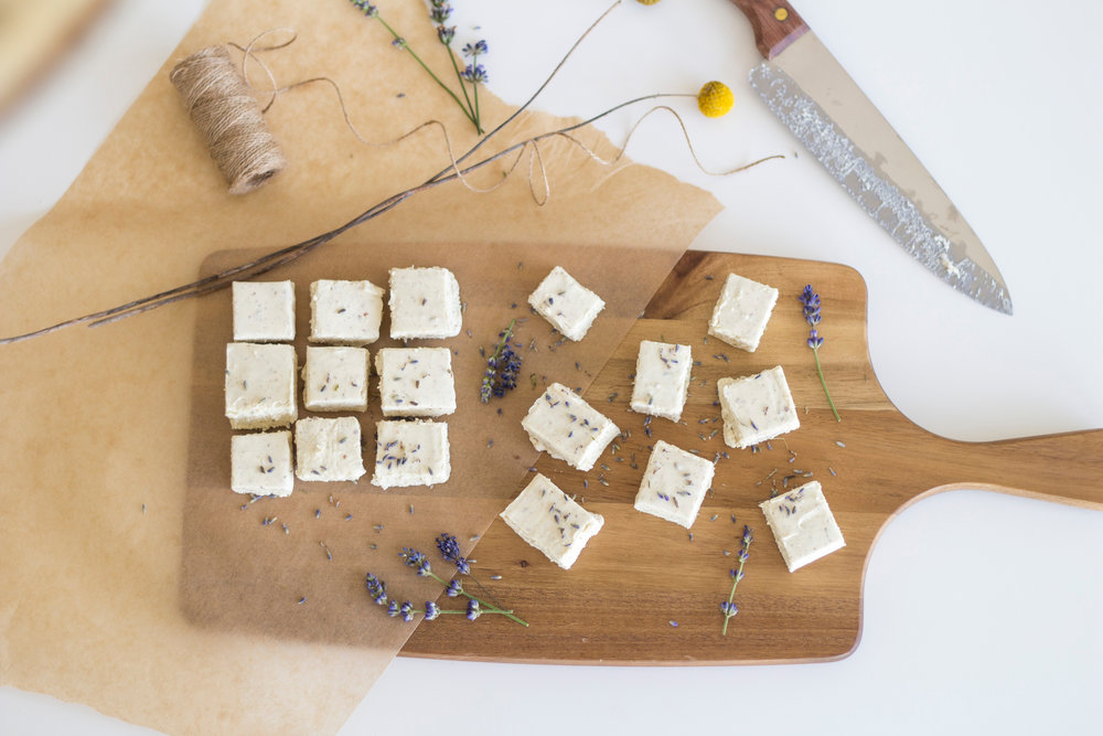 Fall is right around the corner and has us so excited for all the fun concoctions we can make with our lavender. Our harvest is beginning to wind down, and we love to spend the cooler days cooking up recipes with our dried culinary lavender.  This month, the recipe that comes to mind is this white chocolate lavender fudge. Fudge is a perfect recipe for this time of year as it makes for a yummy after school treat, a unique dessert to bring into the office, or even wrapped as a teacher appreciation gift. This recipe is a unique spin on classic chocolate fudge with a dash of our beautiful lavender. The culinary lavender gives this fudge a light purple hue and is an impressive treat whether it's just for you or to share!  Ingredients: 14oz sweetened condensed milk ¼ cup heavy whipping cream 1 tbsp ground lavender 1 stick unsalted butter ¾ tsp kosher salt 1 bag white chocolate chips 1 jar marshmallow fluff  Directions: In a double boiler, stir in cream, condensed milk, ground lavender, butter, salt, white chocolate chips, and fluff. Stir until temperature is 240 F and almost boiling. Pour into greased 8x8 pan and chill in refrigerator until set. Cut into bite size squares. Serve and enjoy!   Hugs, Christina   Recipe made exclusively for Sweet Streams Lavender Co. by Food Gal Al.  Photography by Grace Pritchett