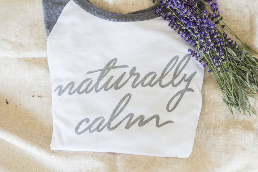 Our  Naturally Calm t-shirt  is the perfect shirt to slip into after hot yoga or cozy up in to sip your morning coffee or tea or juice. In a world where we are hyper-connected, dialed-in, plugged-in, on-the- go, and driven to be the best, our Naturally Calm t-shirt reminds us that it is ok to pause, take a break, and breathe. Super soft cotton (my favorite thing about the shirt), fabric t-shirt is made in the USA and may-or- may not smell like our lavender farm when it arrives to you! If you are local to KC it is available in the pop up shop in Leawood, KS Handmade Holidays so you can try it on.   The Naturally Calm t-shirt reminds us of lavender and all the benefits it provides, such as calmness, serenity, and simplicity. This is my favorite shirt to wear around the house, gardening, or going on walks.   The fabric is easy and breathable. This sweet shirt also makes a good gift or stocking stuffer to the yogi or the person who needs a little more calm in your life. Our Naturally Calm t-shirt is available in sizes S-XXL on our website. Get yours today!    Hugs, Christina