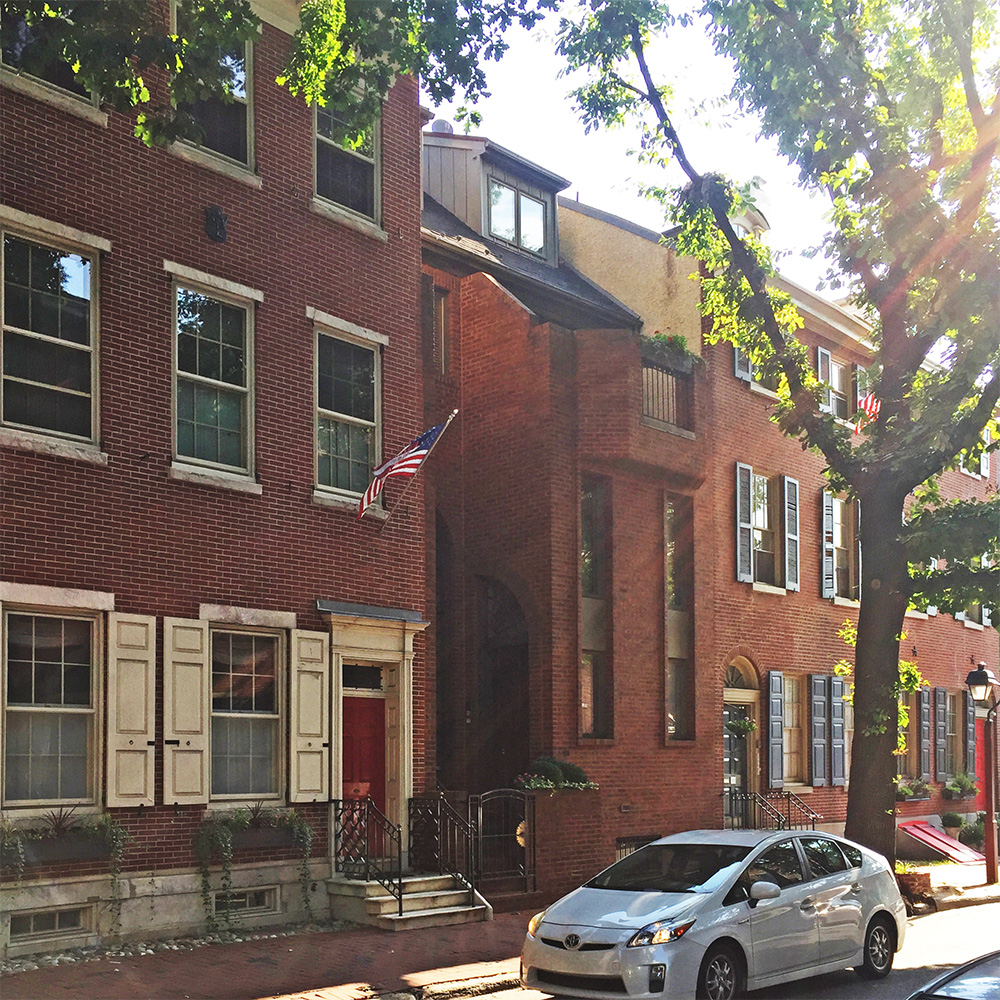 Photo of a Brick Modern home in Society Hill squeezed in between two colonial homes.