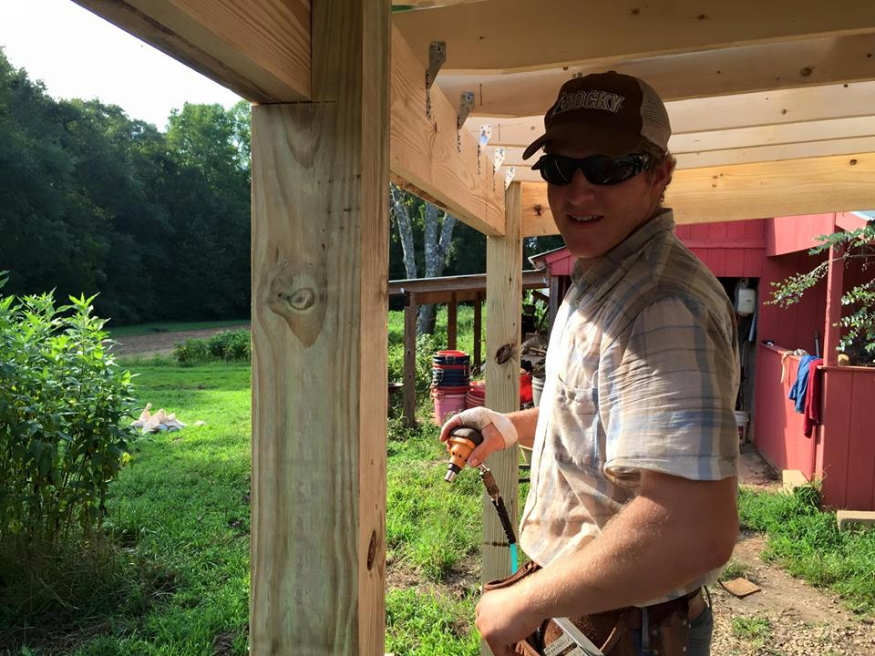 Gillen, Nicolas's oldest son, building the Farm's new outdoor wash station. While he is a skilled carpenter creating his own business, he still finds time to help his Dad on the Farm.