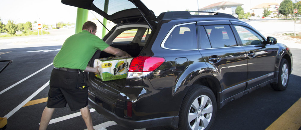 A Lyft driver loads goods into his car at a Walmart as part of the retailer's trial program to have Lyft and Uber drivers make deliveries.