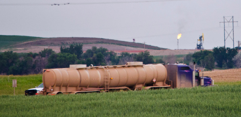 An empty oil truck passes in front of oil wells flaring gas in McKenzie County west of Watford City, North Dakota. Few pipelines exist in North Dakota, so most oil is trucked out daily from each well.  (Photo:  Tim Evanson , Wikimedia Commons)