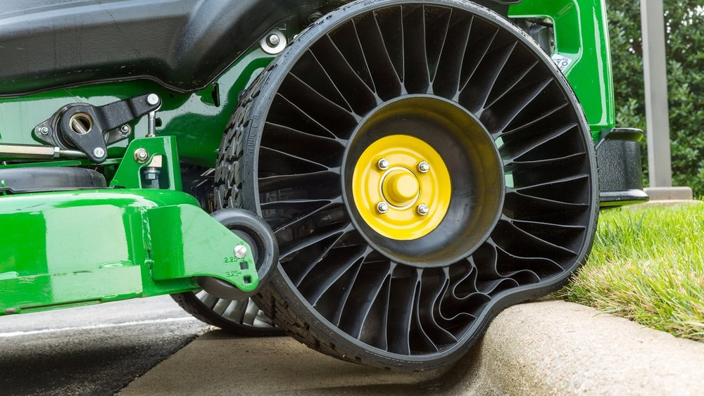 A lawnmower's airless tire deforms as it rolls over a curb.