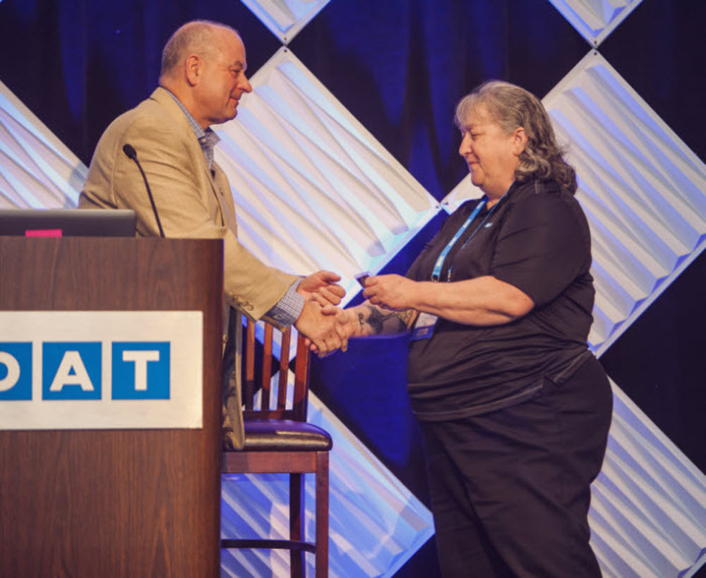 "DAT's Tami Hart received a ""challenge coin"" for her work in helping the Georgia Bureau of Investigation solve fraud crimes. ( Photo: DAT Solutions )"