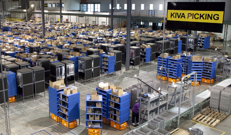 The interior of an Amazon fulfillment center with robotic pickers is pictured.