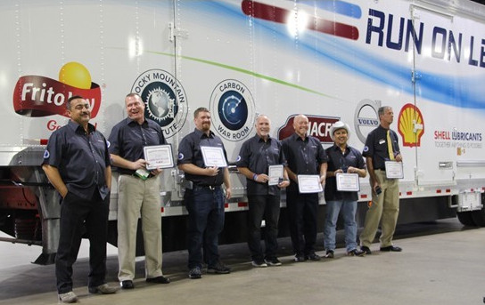 The seven drivers who participated in the Run on Less challenge last fall pose for a group photo at the North American Commercial Vehicle Show in October.