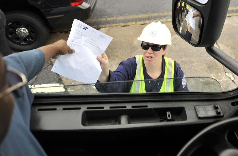 A truck driver hands over documents to a US Coast Guard petty officer. A new system that could have cause delays is being delayed. ( Photo: Port Security USA )
