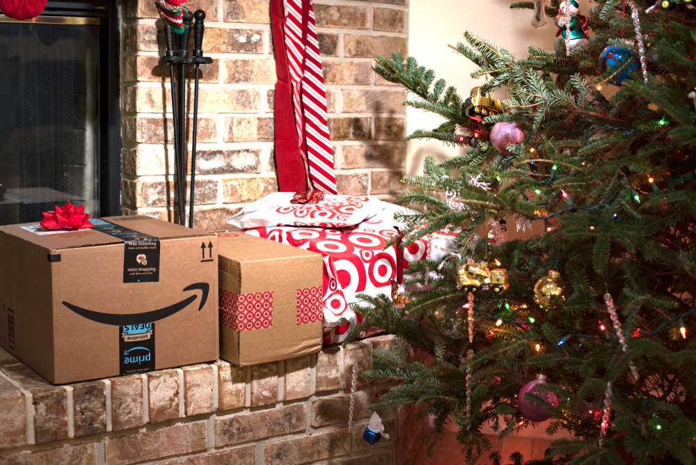 Shipping packages from Amazon Prime and Target store on a fireplace mantle hearth beside the Christmas tree.  (Photo: Shutterstock)