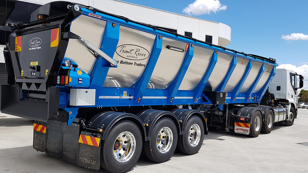 Pictured - a live bottom trailer. They have conveyor belts built into the trailer and do not tip. They are used to carry materials such as aggregates. As they don't tip, they are safer than tip-trucks on uneven ground or under low-hanging power-lines. (Photo: MaxiTrans / Trout River Australia).
