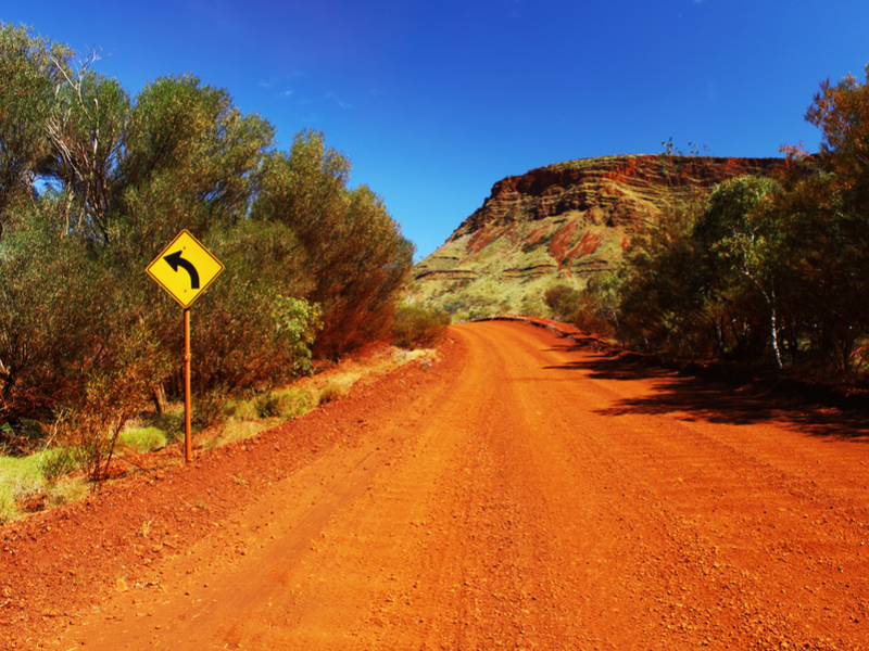 A turn-left sign on an unsealed Outback road in Karijini National Park Western Australia. (Photo: Shutterstock).