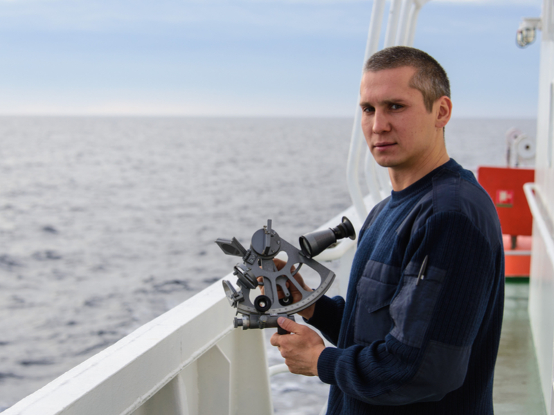 Pictured: a young deck officer who is holding a sextant, a marine navigation tool used to measure the angular distance between two visible objects. Young deck officers are an increasingly endangered species in Australia, according to a new report.  Photo: Shutterstock.