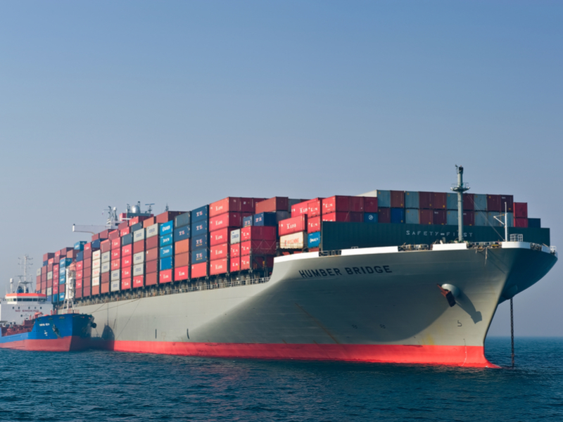 Pictured: a large boxship appears to be receiving fuel oil from a small bunker tanker (bottom left);  Photo: Shutterstock