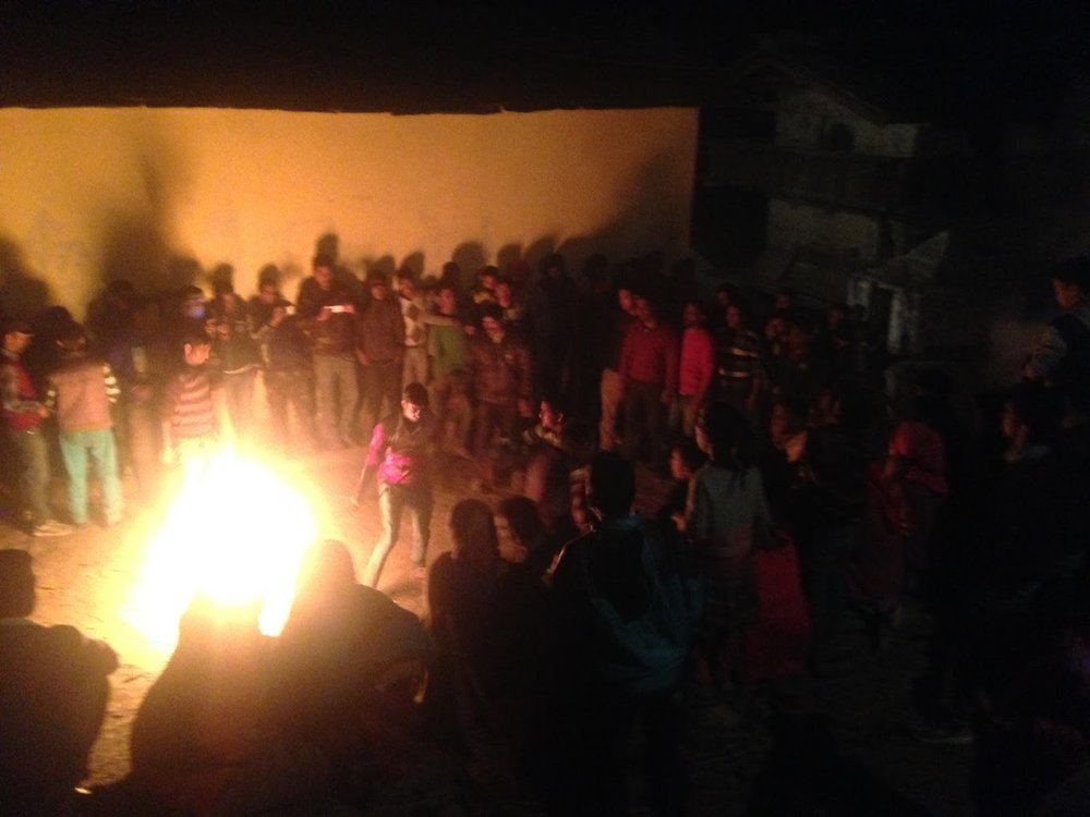 Diwali in the Himalays; villages gleefully watch a man spinning and jumping over burning logs