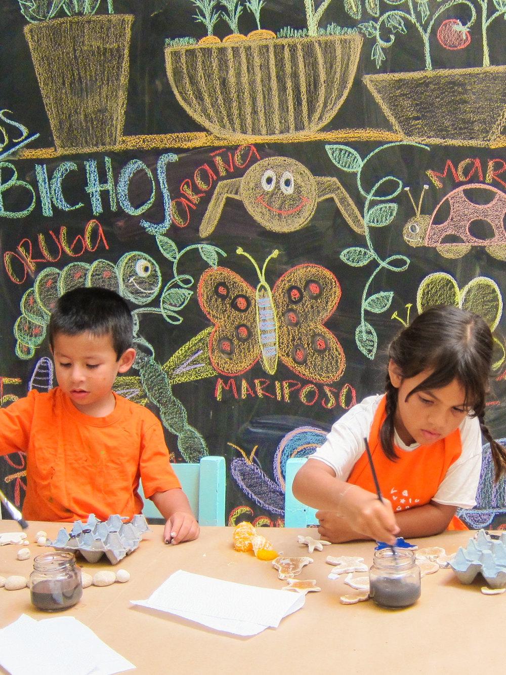 Los niños pintando para decorar el huerto.