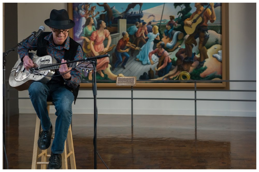 "Photo by Kim Peery Sherman at the Country Music Hall of Fame in Nashville, February 2017 at a guitar and banjo demonstration. The painting in the background is "" The Sources of Country Music "" by Thomas Hart Benton."