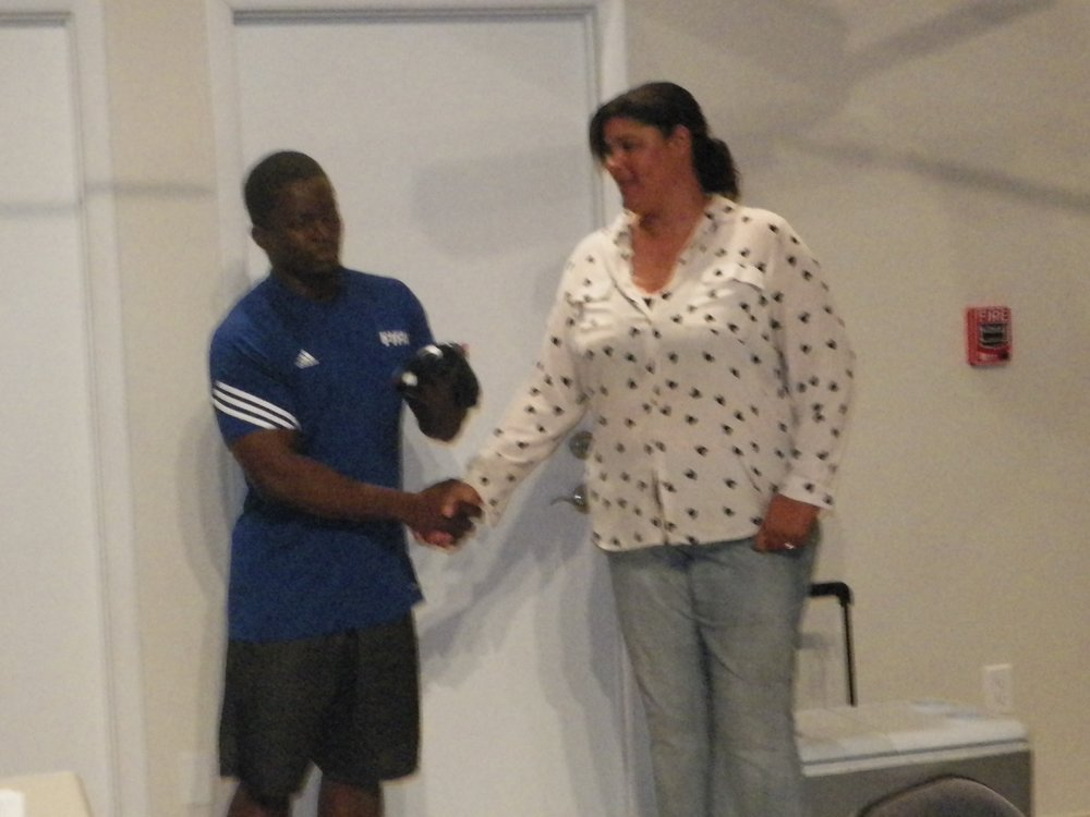 Player Peterson Evariste presenting thank yous to sponsor, Crust Bakery.jpg