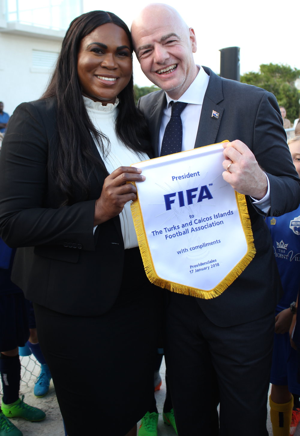 FIFA President Gianni Infantino gifts TCIFA President Sonia Bien-Aime with a FIFA pennant
