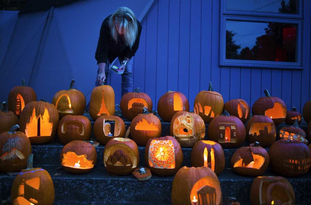 "Image and caption from the 2016 Daily Egyptian coverage of this event:   Lindy Loyd, a Bucky Dome board member, lights jack-o'-lanterns Monday, Oct. 31, 2016, at the Buckminster Fuller Dome Home in Carbondale. The pumpkins, carved by SIU architecture and interior design students, were displayed for visitors and trick or treaters to view. ""No one else is doing anything like this,"" architecture professor Jon Davey said. ""It gives the students a good time."" The students were assigned to carve the pumpkins over the weekend. Amongst nearly 80 pumpkins, designs included the Statue of Liberty, the Eiffel Tower and the U.S. Capitol Building. (Ryan Michalesko 