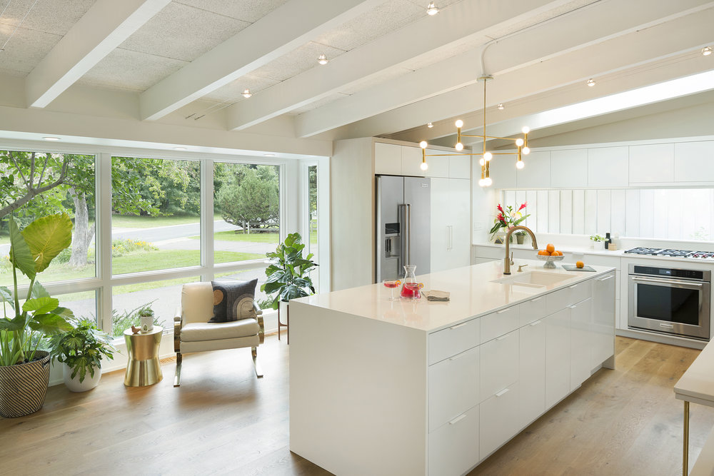In this kitchen design, biophilic elements are widely present with unobstructed views of nature and potted plants indoors. / Design by    Vela Creative   , Photo by Spacecrafting