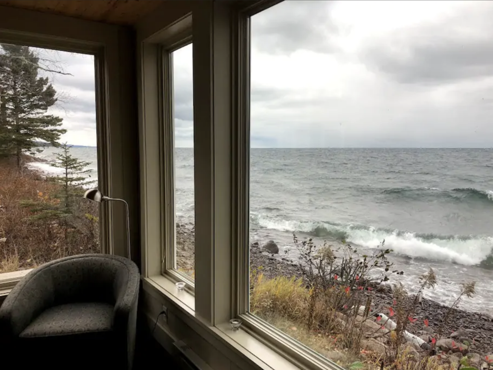 A picture window provides up-close views of the waves of Lake Superior and provides the perfect cozy nook for relaxing. /  Source