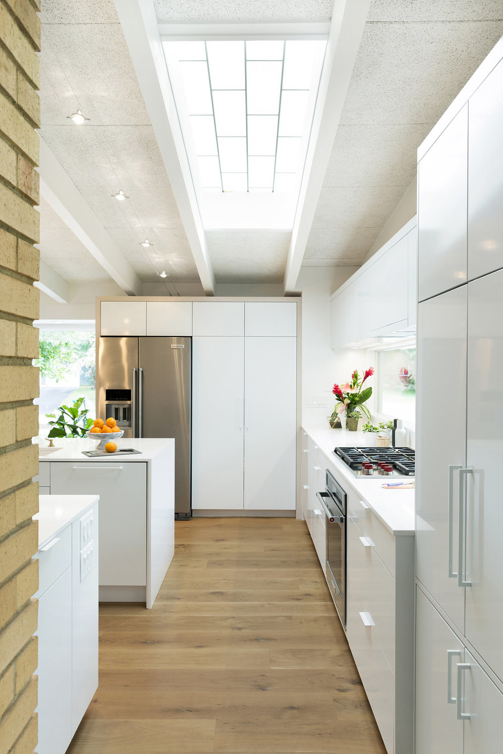 A skylight in our Midcentury Revitalization kitchen provides natural light throughout the day, creating interest via shifting shadow patterns on the floor as the sun changes its position. / Source:    Vela Creative