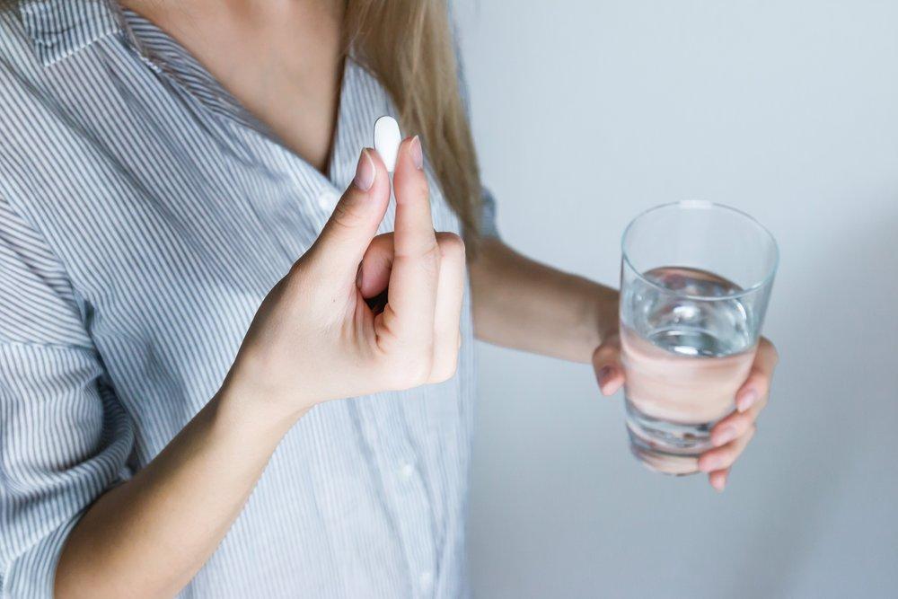Woman taking pain killer pill
