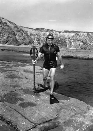 Prime Minister Harold Holt in his preferred hide and seek uniform of short wetsuit, flippers, mask, snorkel and huge spear gun.