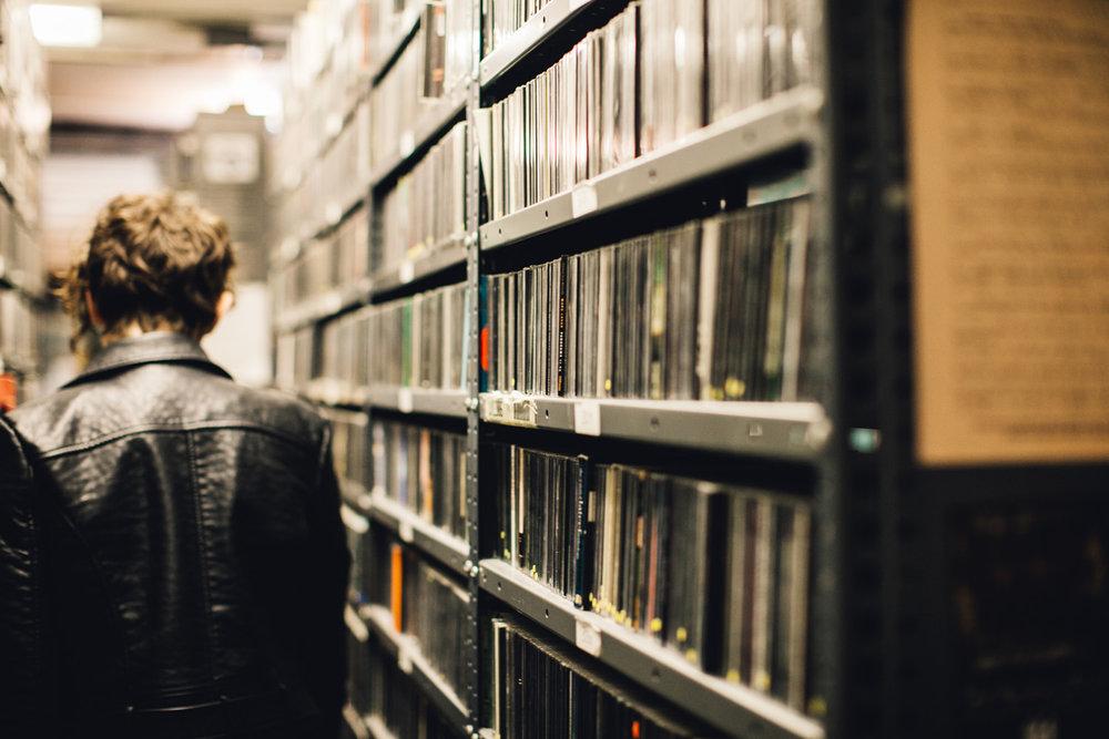 Woman walking amongst shelves of CDs