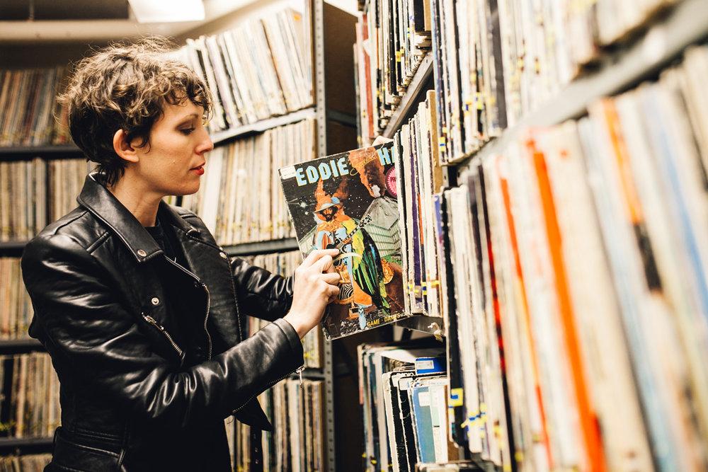 Woman putting vinyl record on shelf