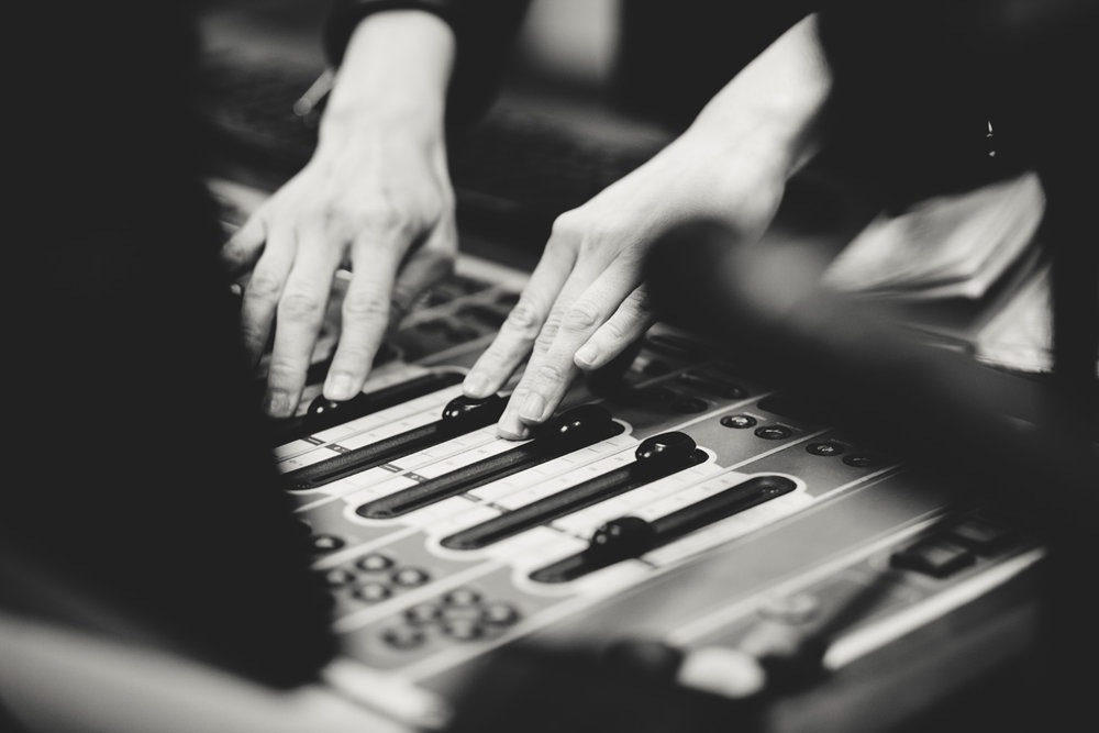 Female radio DJ with hands on mixing board