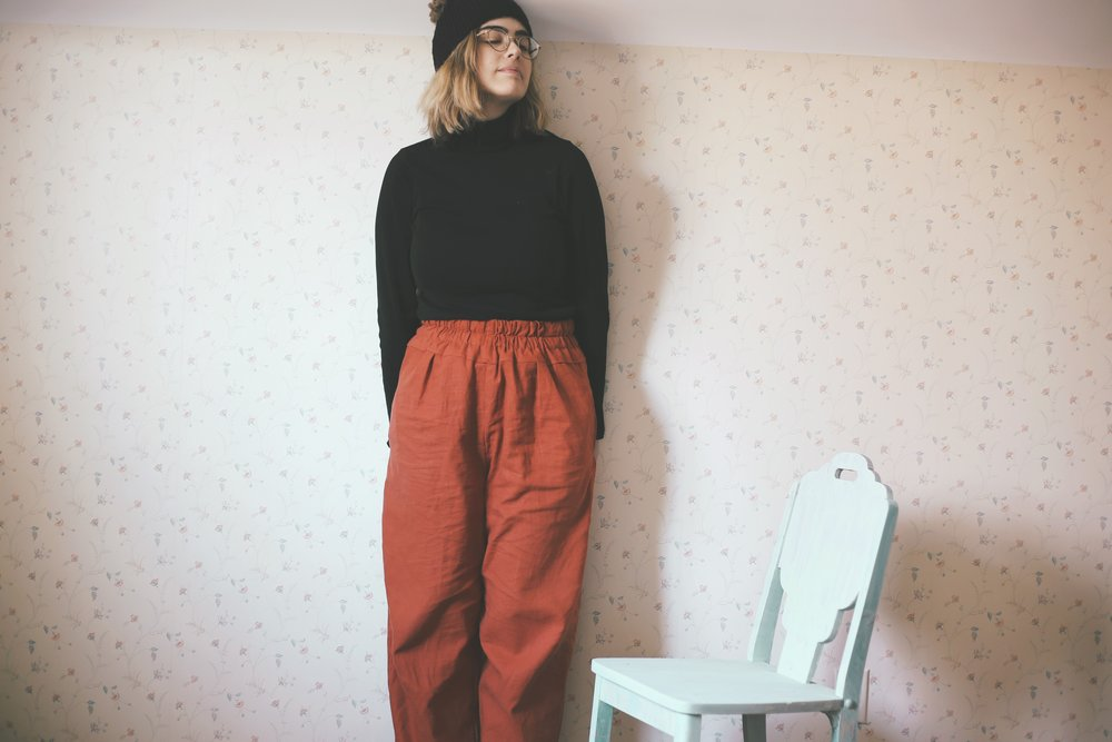 A woman poses in handmade pants and a crochet hat