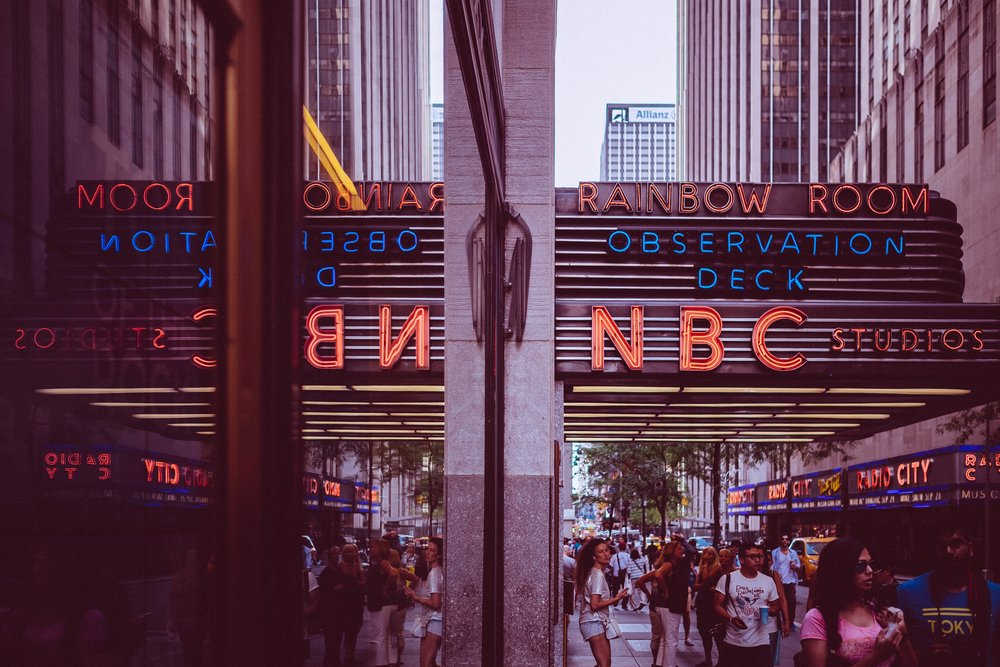 The exterior of NBC Studios, home of SNL, with people walking by