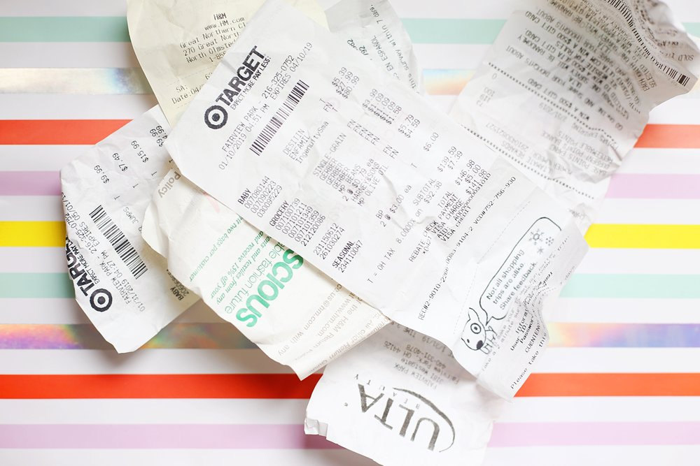 A pile of receipts on a colorful striped background