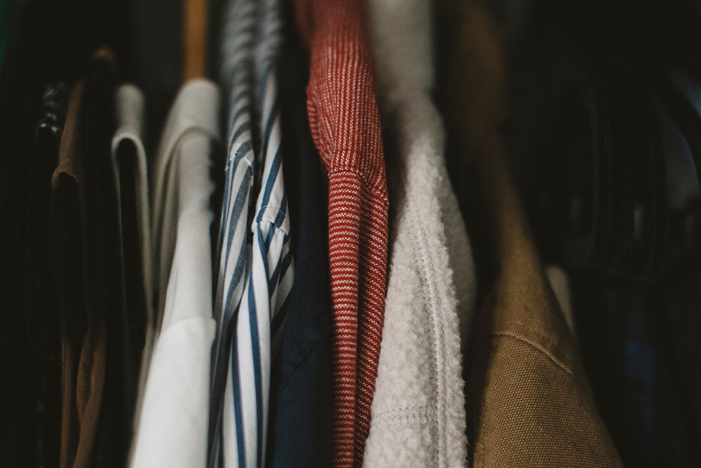 A closeup of clothing hanging in a closet